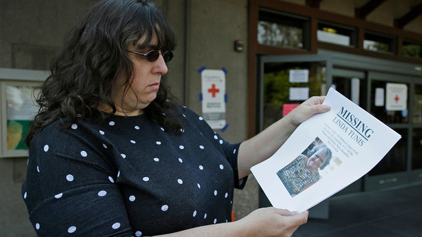 Jessica Tunis stands outside a Red Cross evacuation center and holds a flyer about her missing mother Oct. 11, 2017, in Santa Rosa, Calif.