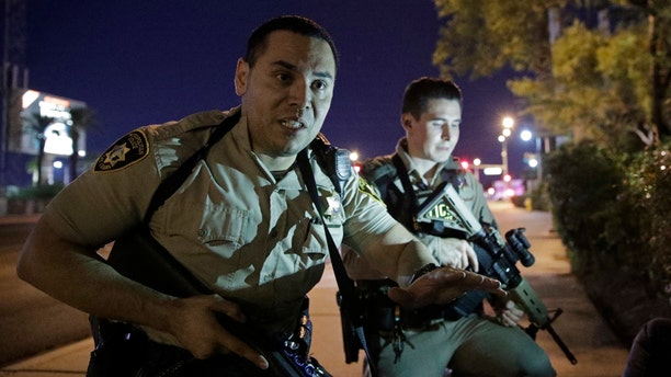 Police officers advise people to take cover near the scene of the mass shooting near the Mandalay Bay resort and casino on the Las Vegas Strip on Sunday, Oct. 1. Police said a 64-year-old gunman on the 32nd floor of the hotel rained down gunfire on thousands of concertgoers, killing at least 50.