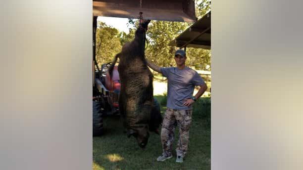 Joe Clowers of Union Grove, Texas is seen with the massive wild hog that he killed in his backyard.