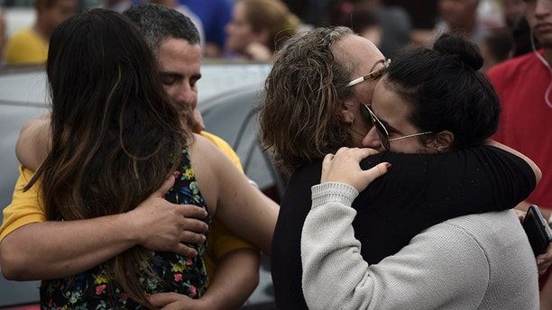 Relatives comfort each other as the body of a family member is removed at an early morning crime scene in San Juan