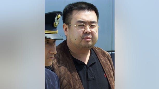Kim Jong Nam is escorted by police as he boards a plane upon his deportation from Japan at Tokyo's Narita international airport May 4, 2001.