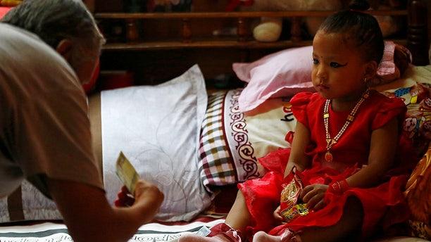 A man offers money to the newly appointed Living Goddess Kumari of Kathmandu Trishna Shakya, 3.