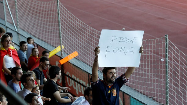 """A man displays a banner that reads """"Pique Out"""", referring to Spain's player Gerard Pique, before a training session in Las Rozas, near Madrid, Spain, October 2, 2017. REUTERS/Rafael Marchante - RC1F625D9820"""