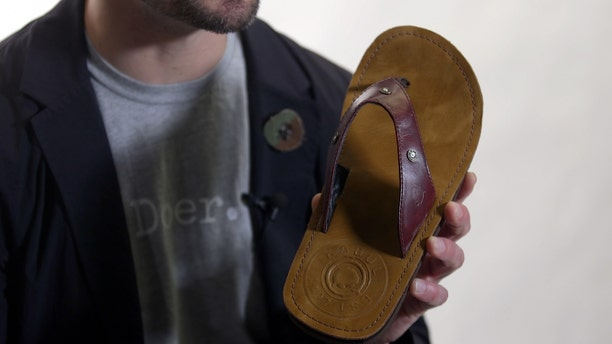 Combat Flip Flop co-founder and army veteran Matthew Griffin displays the AK-47 flip flop.