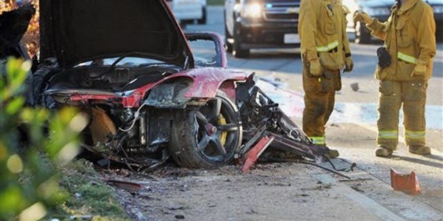 Sheriff's deputies work near the wreckage of the Porsche that crashed into a light pole and killed actor Paul Walker and Roger Rodas in Valencia, Calif., on Nov. 30, 2013.