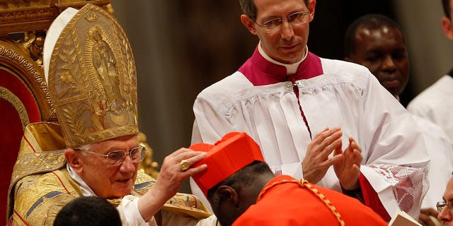 Cardinal Robert Sarah of Guinea receives the red biretta, a four-cornered red hat, from Pope Benedict XVI during the Consistory ceremony in Saint Peter's Basilica at the Vatican November 20, 2010.
