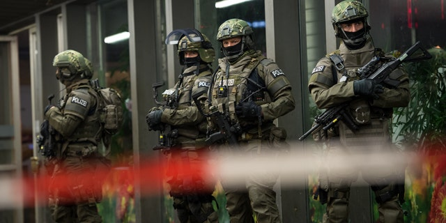 German special police stand in front of the Munich, southern Germany, main train station Thursday evening, Dec. 31, 2015 after police warned of 'imminent threat' of terror attack and ordered two train stations to be cleared. (Sven Hoppe/dpa via AP)