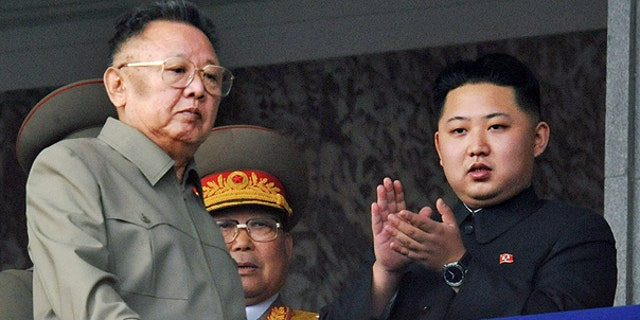 In this Oct. 10, 2010 file photo North Korea leader Kim Jong Il, left, walks by his son Kim Jong Un on the balcony as they attend a massive military parade marking the 65th anniversary of the communist nation's ruling Workers' Party in Pyongyang, North Korea.