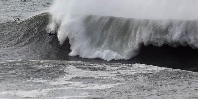 Jan. 8, 2016: A surfer wipes out under a large wave at Mavericks in Half Moon Bay, Calif.