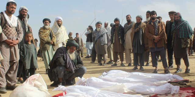 FILE -- In this Nov. 4, 2016 file photo, Afghan villagers gather around several victims' bodies who were killed during clashes between Taliban and Afghan security forces in the Taliban-controlled, Buz-e Kandahari village in Kunduz province, Afghanistan.