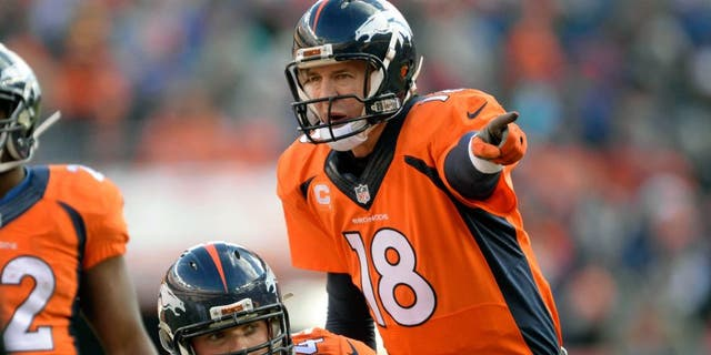 Dec 28, 2014; Denver, CO, USA; Denver Broncos quarterback Peyton Manning (18) calls an audible over center Will Montgomery (64) in the first quarter against the Oakland Raiders at Sports Authority Field at Mile High. Mandatory Credit: Ron Chenoy-USA TODAY Sports