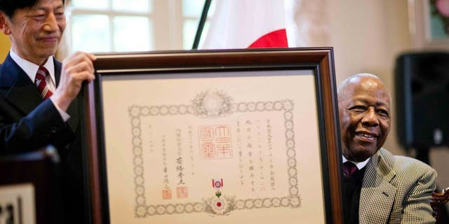 Hank Aaron, right, is presented with a framed certificate for the Order of the Rising Sun, Gold Rays with Rosette, by Takashi Shinozuka, left, Consul General of Japan in Atlanta, during a ceremony at the consul general's home, Thursday, Jan. 14, 2016, in Atlanta. Japan has honored the former home run king with one of its highest awards, bestowing the Order of the Rising Sun for bringing young people and countries together through baseball. (AP Photo/David Goldman)