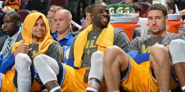 CLEVELAND, OH - JANUARY 18: Stephen Curry #30 of the Golden State Warriors smiles while resting on the bench along side Draymond Green #23 an Klay Thompson #11 against the Cleveland Cavaliers on January 18, 2016 at Quicken Loans Arena in Cleveland, Ohio. (Jesse D. Garrabrant/NBAE via Getty Images)
