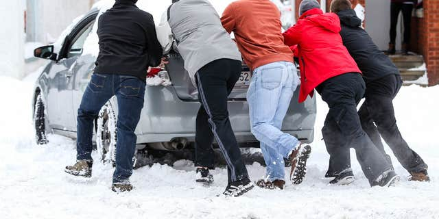 Jan. 23, 2016: A group of friends help push a car into a safe parking spot after it was stuck on a snow-covered road in Huntington, W.Va.
