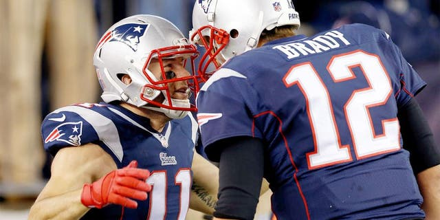 Nov 2, 2014; Foxborough, MA, USA; New England Patriots quarterback Tom Brady (12) congratulates special teams Julian Edelman (11) on scoring a touchdown on a run back return during the second quarter against the Denver Broncos at Gillette Stadium. Mandatory Credit: Greg M. Cooper-USA TODAY Sports