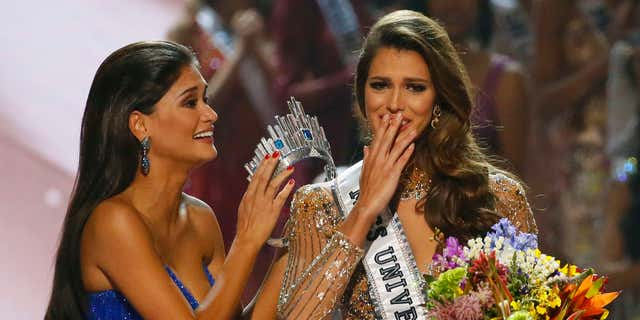Miss Universe 2015 Pia Wurtzbach, left, prepares to crown Iris Mittenaere of France shortly after being proclaimed the Miss Universe 2016 in coronation Monday, Jan. 30, 2017, at the Mall of Asia in suburban Pasay city, south of Manila, Philippines.