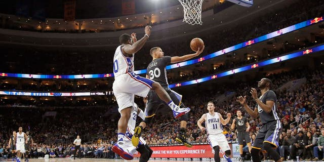 Golden State Warriors' Stephen Curry (30) goes up for a shot past Philadelphia 76ers' Isaiah Canaan (0) during the first half of an NBA basketball game Saturday, Jan. 30, 2016, in Philadelphia. (AP Photo/Matt Slocum)