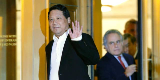 """FILE- In this Oct. 26, 2015 file photo, Chinese billionaire Ng Lap Seng waves to the media as he leaves federal court after he was released on bail in connection with a United Nations bribery scheme in New York. Jurors in Ng's trial should know he was referred to as the """"boss"""" by co-conspirators, prosecutors said Friday, Dec. 30, 2016, as they argued that defense lawyers were """"far-fetched"""" to say the word suggests organized crime. (AP Photo/Kathy Willens, File)"""