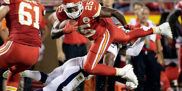 FILE - In this Sept. 17, 2015, file photo, Kansas City Chiefs running back Jamaal Charles (25) is tackled by Denver Broncos cornerback Chris Harris Jr., rear, during the second half of an NFL football game in Kansas City, Mo. Adrian Peterson and Jamaal Charles, both stalwarts for their previous clubs and with All-Pro credentials, are out there. But how many 30-plus running backs get long-term deals, even proven ones such as these? And both will want big bucks. (AP Photo/Charlie Riedel, File)