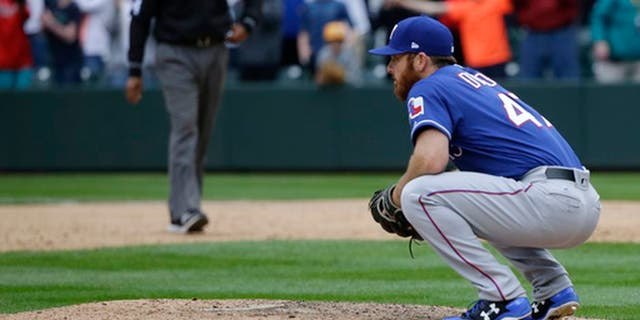 Texas Rangers closing pitcher Sam Dyson crouches on the mound after he gave up a walk-off RBI single to Seattle Mariners' Nelson Cruz in the ninth inning of a baseball game, Sunday, April 16, 2017, in Seattle. The Mariners won, 8-7. (AP Photo/Ted S. Warren)