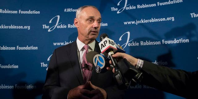 """FILE - In this April 27, 2017, file photo, Major League Baseball Commissioner Rob Manfred speaks to reporters after a ceremonial ground breaking for the Jackie Robinson Museum in New York. Days after a fan at Fenway Park directed racial slurs at Baltimore Orioles outfielder Adam Jones, Manfred said he is determined to """"provide our players with an environment where they feel comfortable in every major league stadium that they play."""" (AP Photo/Mary Altaffer, File)"""
