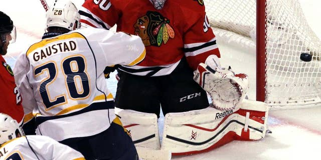 Chicago Blackhawks goalie Corey Crawford, right, blocks a shot by Nashville Predators center Paul Gaustad (28) during the third period in Game 6 of an NHL Western Conference hockey playoff series Saturday, April 25, 2015, in Chicago. The Blackhawks won 4-3. (AP Photo/Nam Y. Huh)