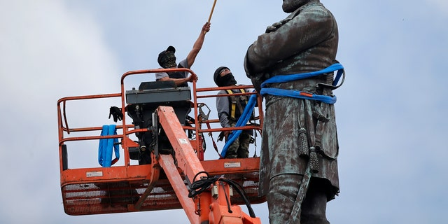 In this May 19, 2017, file photo, workers prepare to take down the statue of former Confederate general Robert E. Lee, which stands over 100 feet tall, in Lee Circle in New Orleans.