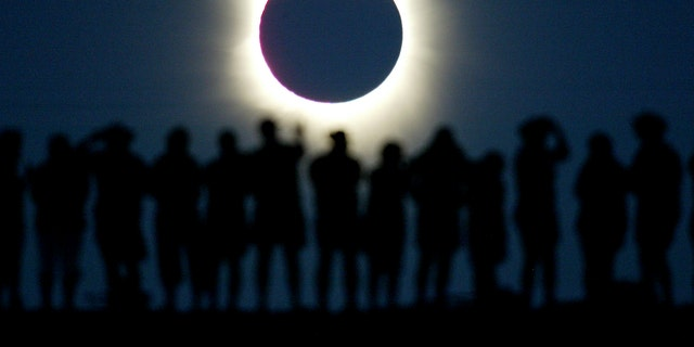 Tourists watch the sun being blocked by the moon during a solar eclipsein the Australian outback town of Lyndhurst, located around 700kilometres (437 miles) north of Adelaide December 4, 2002. The town isone of only four in Australia where the 26 second-long full eclipse ofthe sun could be seen and occurred during celebrations for the Year ofthe Outback. The shadow path of whats called totality, where the'diamond ring' effect becomes visible, can be seen on a path that isjust 36 kilometres wide. REUTERS/David GrayDG/CP - RTREU1E