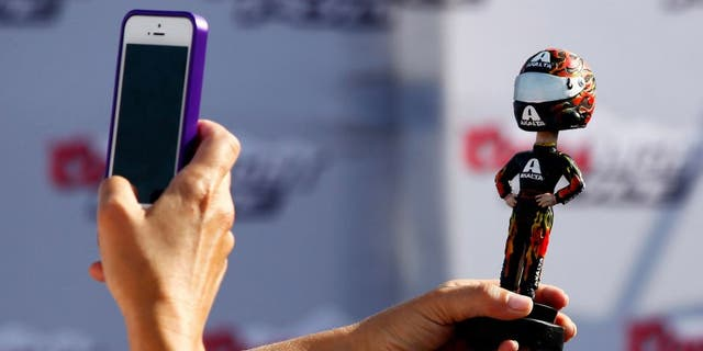 BROOKLYN, MI - AUGUST 16: A fan takes a picture of a bobblehead during practice for the NASCAR Sprint Cup Series Pure Michigan 400 at Michigan International Speedway on August 16, 2014 in Brooklyn, Michigan. (Photo by Brian Lawdermilk/NASCAR via Getty Images)