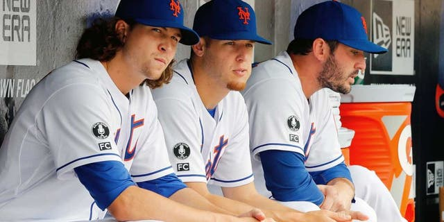 NEW YORK, NY - AUGUST 03: (L-R) Jacob deGrom #48, Zack Wheeler #45 and Matt Harvey #33 of the New York Mets look on against the San Francisco Giants at Citi Field on August 3, 2014 in the Flushing neighborhood of the Queens borough of New York City. The Giants defeated the Mets 9-0. (Photo by Jim McIsaac/Getty Images)
