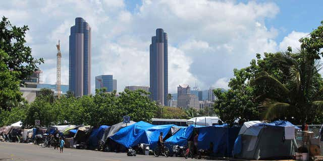 FILE - In this June 30, 2015, file photo, people camp out on a sidewalk in the Kakaako neighborhood of Honolulu, Hawaii.