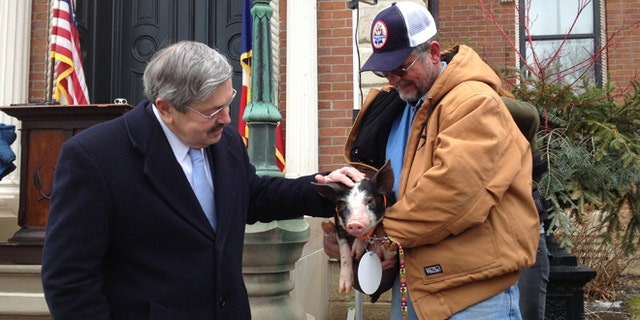 Feb. 8, 2013: Iowa Gov. Terry Branstad, left, pardons a Berkshire pig named Bonnie, held by her owner Randy Hilleman, at the governor's mansion in Des Moines, Iowa.