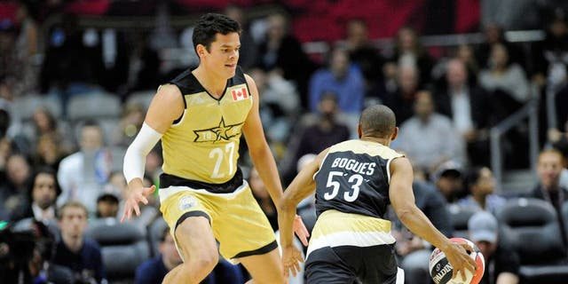 Feb 12, 2016; Toronto, Ontario, Canada; USA player Muggsy Bogues (5'3) is defended by Canada player Milos Raonic (27) during the All-Star celebrity basketball game at Ricoh Coliseum. Mandatory Credit: Peter Llewellyn-USA TODAY Sports