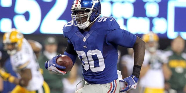 Nov 17, 2013; East Rutherford, NJ, USA; New York Giants defensive end Jason Pierre-Paul (90) runs back an interception against the Green Bay Packers for a touchdown during the fourth quarter of a game at MetLife Stadium. Mandatory Credit: Brad Penner-USA TODAY Sports