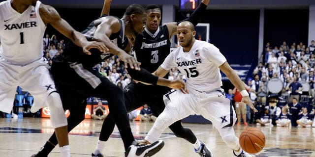 Xavier's Myles Davis (15) drives against Providence's Kris Dunn (3) and Kris Dunn, second from left, during the second half of an NCAA college basketball game Wednesday, Feb. 17, 2016, in Cincinnati. Xavier won 85-74. (AP Photo/John Minchillo)
