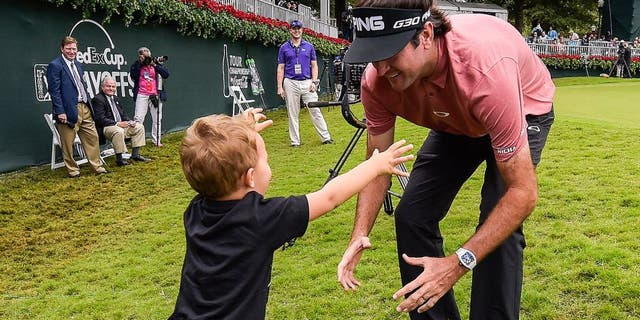 ATLANTA, GA - SEPTEMBER 27: Bubba Watson hugs his son Caleb on the 18th hole green following the final round of the TOUR Championship by Coca-Cola, the final event of the FedExCup Playoffs, at East Lake Golf Club on September 27, 2015 in Atlanta, Georgia. (Photo by Stan Badz/PGA TOUR)