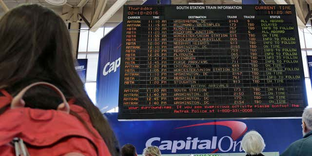 Feb. 18, 2016: With many delays and cancelations posted, travelers watch the train departure board at South Station in Boston.