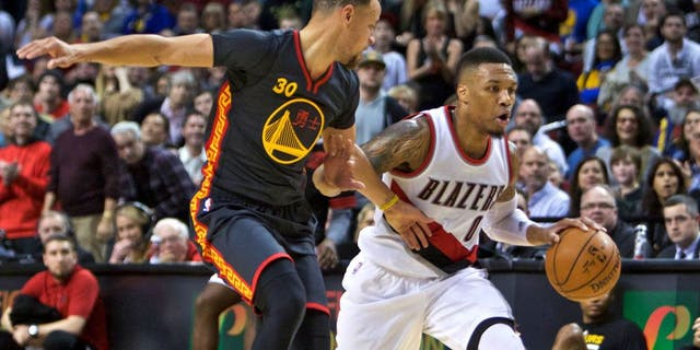Portland Trail Blazers guard Damian Lillard moves the ball past Golden State Warriors guard Stephen Curry, left, during the second half of an NBA basketball game in Portland, Ore., Friday, Feb. 19, 2016. (AP Photo/Craig Mitchelldyer)