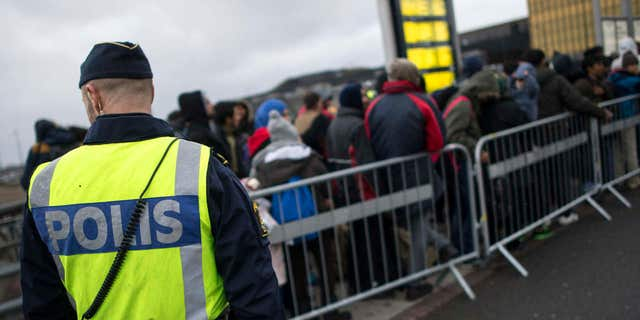 Nov. 19, 2015: A police officer keeps guard as migrants arrive at Hyllie station outside Malmo, Sweden.