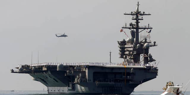 FILE - In this Aug. 22, 2014 file photo, the aircraft carrier USS Carl Vinson sails out of San Diego Harbor leaving for a nine month deployment in San Diego.