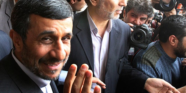 Feb. 20: Iranian President Mahmoud Ahmadinejad waves to the media as he leaves the parliament in Tehran.