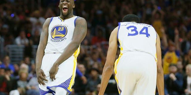 Golden State Warriors' Draymond Green, left, and Shaun Livingston, right, celebrate a 3-pointer by teammate Harrison Barnes, not seen, during the second half of an NBA basketball game against the Los Angeles Clippers, Saturday, Feb. 20, 2016, in Los Angeles. The Warriors won 115-112. (AP Photo/Danny Moloshok)