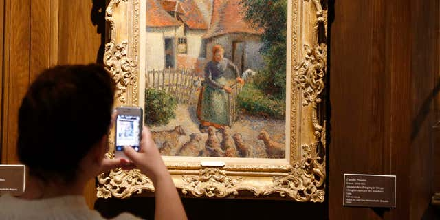 """FILE - In this Feb. 8, 2014, file photo, a visitor to the Fred Jones Jr. Museum of Art at the University of Oklahoma in Norman, Okla., takes a photograph of a piece called """"Shepherdess Bringing in Sheep"""" by French impressionist artist Camille Pissarro, at the museum."""
