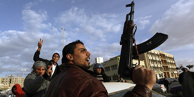 Feb. 23: A Libyan protester holds a weapon as he shouts slogans against Libyan Leader Muammar Qaddafi, during a demonstration in Tobruk, Libya.
