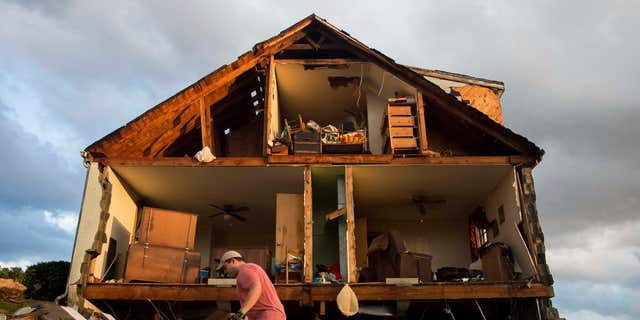 Nick Mobley helps clean up a house owned by a family friend, Wednesday, Feb. 24, 2016, after a storm hit Appomattox County, Va.