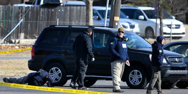 Feb. 26, 2016: FBI agents search the parking lot at Excel Industries, the scene of Thursday's shooting, in Hesston, Kan.
