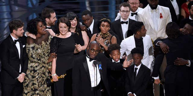 "Barry Jenkins, foreground center, and the cast accept the award for best picture for ""Moonlight"" at the Oscars on Sunday, Feb. 26, 2017, at the Dolby Theatre in Los Angeles."