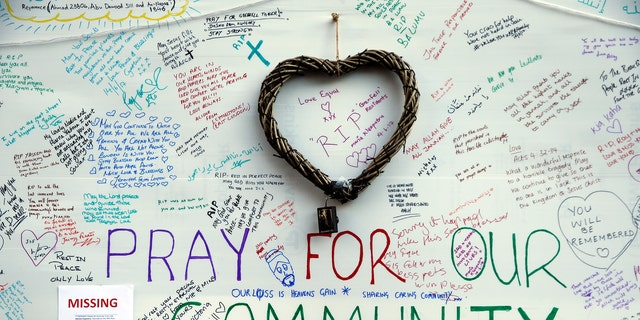 Messages of support for those affected by the massive fire in Grenfell Tower are displayed on a well near the tower in London, Thursday, June 15, 2017. A massive fire raced through the 24-story high-rise apartment building in west London early Wednesday. (AP Photo/Alastair Grant)