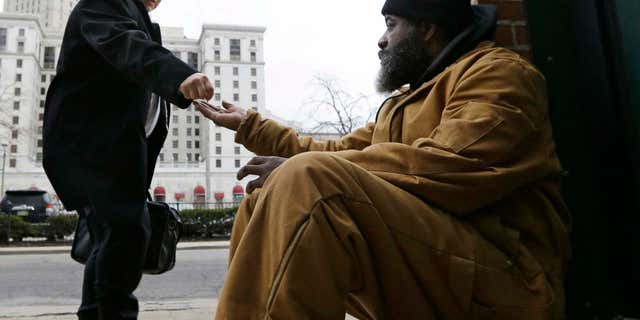 Kenny Chapman, right, 53, receives coins from a man, Tuesday, Feb. 28, 2017, in downtown Cleveland.