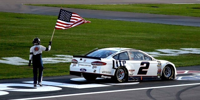 LAS VEGAS, NV - MARCH 06: Brad Keselowski, driver of the #2 Miller Lite Ford, celebrates with the American Flag after winning the NASCAR Sprint Cup Series Kobalt 400 at Las Vegas Motor Speedway on March 6, 2016 in Las Vegas, Nevada. (Photo by Todd Warshaw/Getty Images)